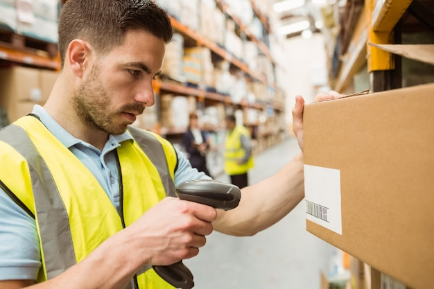 Warehouse worker scanning barcodes on boxes Premium Photo