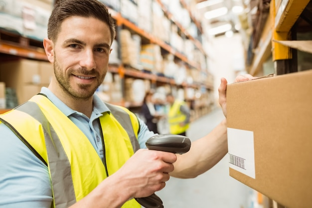Warehouse worker scanning box while smiling at camera Premium Photo