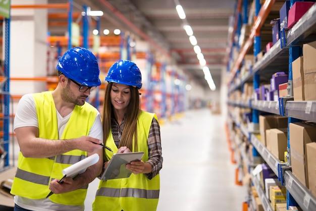 Работники склада проверяют инвентарь и консультируют друг друга по вопросам организации и распределения товаров. Бесплатные Фотографии
