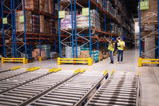 大規模な倉庫で在庫と商品の流通をチェックする倉庫作業員 無料写真