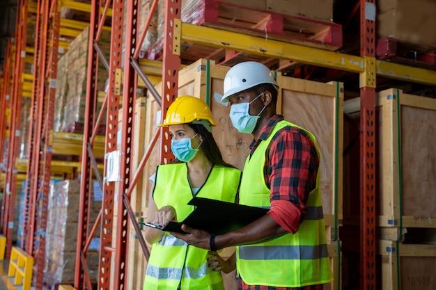 倉庫で働くcovid-19から身を守るために防護マスクをつけている倉庫作業員。 Premium写真