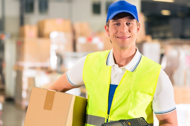Warehouseman with protective vest and scanner, holds package, he standing at warehouse of freight forwarding company Premium Photo