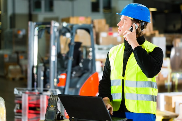 Warehouseman with protective vest, scanner and laptop in warehouse at freight forwarding company using a mobile phone Premium Photo