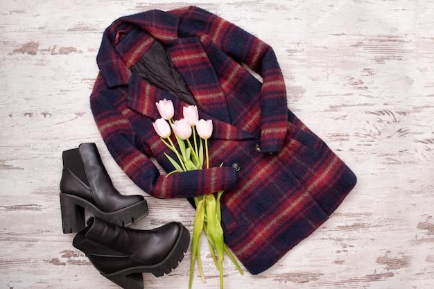 Warm checkered coats, black shoes, tulips. Premium Photo