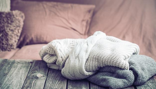 Теплая одежда, вязаные свитера на деревянном столе Premium Фотографии