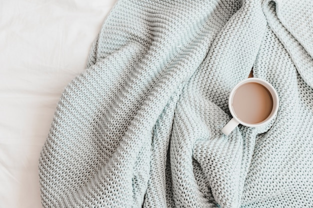 Warm drink in knitting blue plaid on bedsheet Free Photo