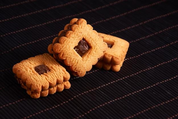赤いスタイルの背景にチョコレートをトッピングした温かい自家製ジンジャースナップクッキー Premium写真