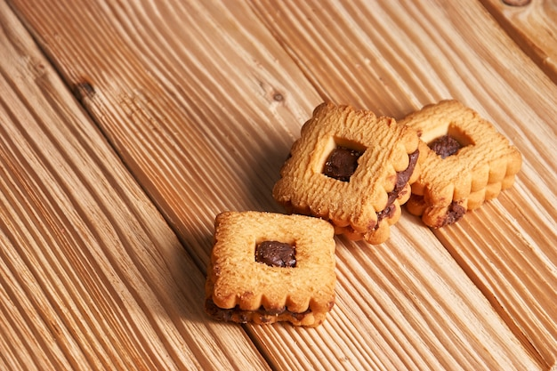 木製のテーブルにチョコレートをトッピングした温かい自家製ジンジャースナップクッキー Premium写真