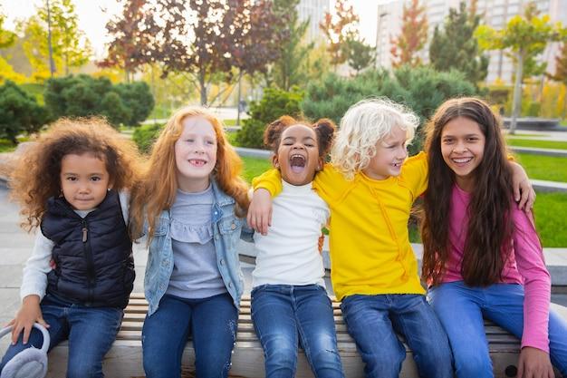 따뜻한. 여름 날에 공원에서 함께 노는 아이, 소녀와 소년의 인종 그룹. 무료 사진
