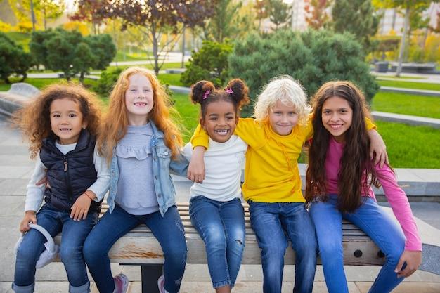 暖かい。夏の日に公園で一緒に遊ぶ子供、女の子、男の子の異人種間のグループ。 無料写真