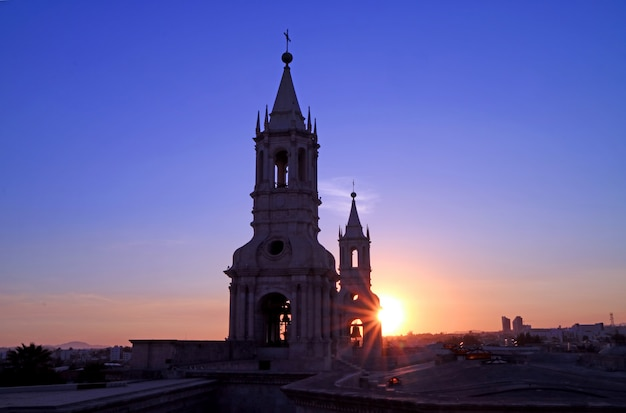 The warm light of setting sun shining through the bell tower of basilica cathedral of arequipa, peru Premium Photo