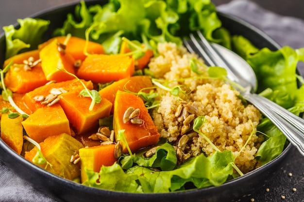 Warm quinoa and pumpkin salad in a white plate on dark background. Premium Photo