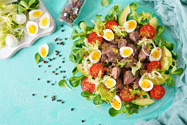 Warm salad from chicken liver, avocado, tomato and quail eggs. healthy dinner. dietary menu. flat lay. top view Free Photo