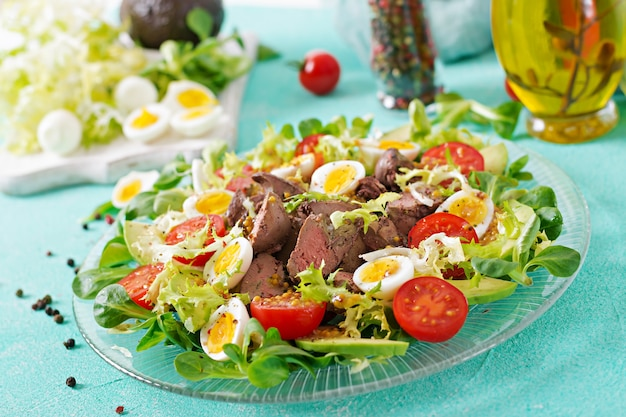 Warm salad from chicken liver, avocado, tomato and quail eggs. healthy dinner. dietary menu. Free Photo