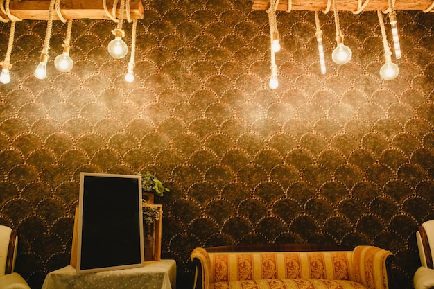 Warm wall decorated with light bulbs and ropes and free room to place text in a empty frame Premium Photo