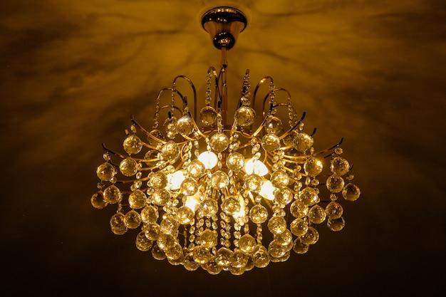 ホールの天井に暖かい白いシャンデリアまたはランプ Premium写真