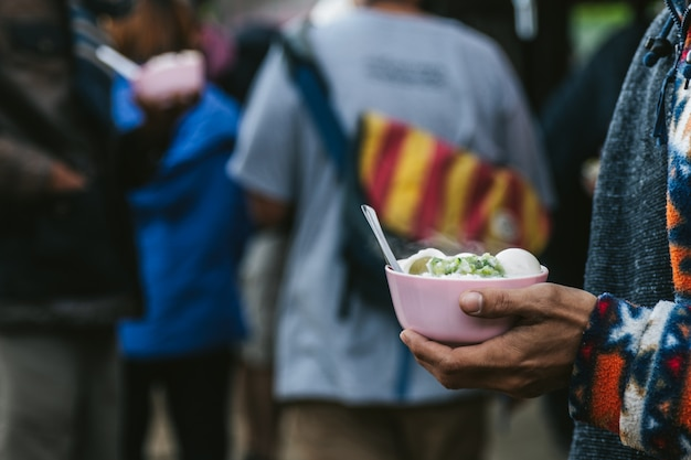 Warming boiled rice in small bowl in hands with steam in the akha village Premium Photo