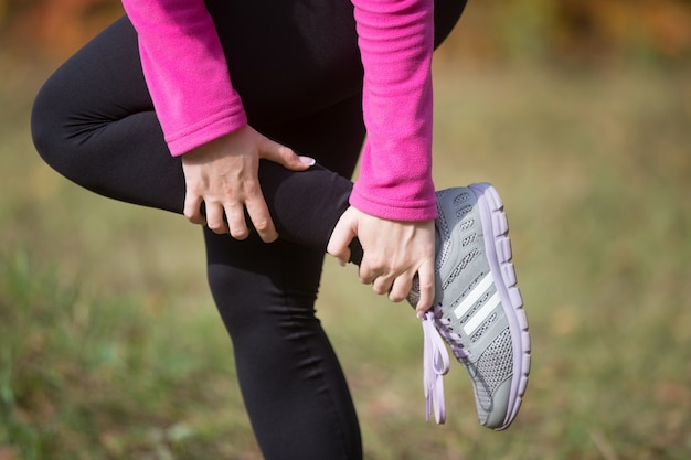 Warming up outdoors in the autumn, holding an ankle Free Photo