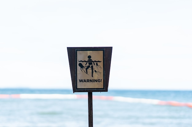 Warning sign, beware about jellyfish on the beach. Premium Photo