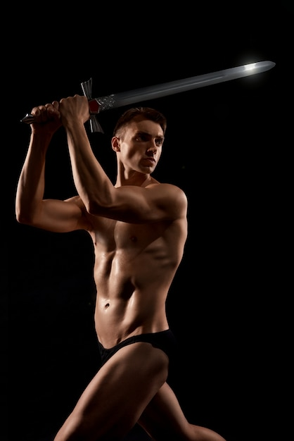 Warrior fight with sword isolated on black. Free Photo