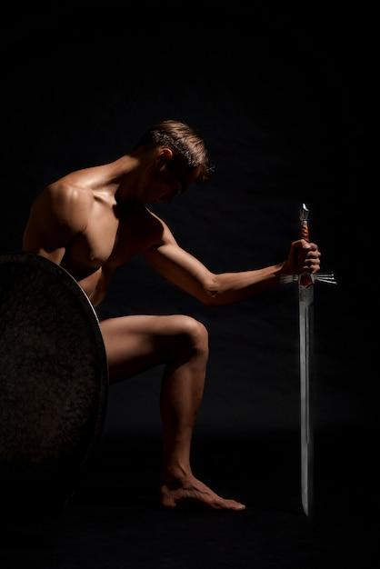 Воин с мечом стоит на коленях. Бесплатные Фотографии