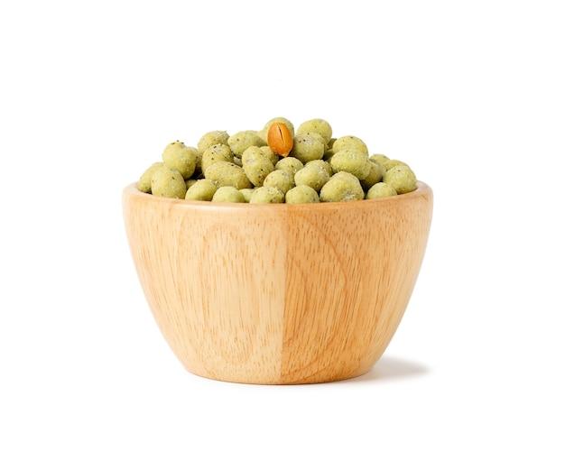 Хрустящие шарики закуски арахиса васаби в деревянной чашке изолированной на белом космосе. Premium Фотографии