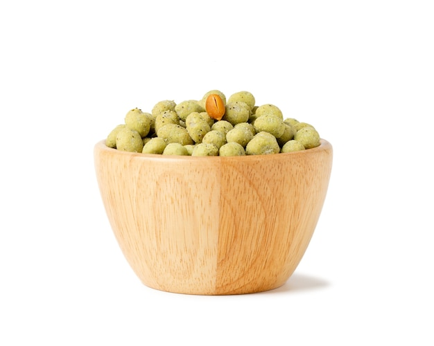 Wasabi crispy peanut snack balls in a wooden cup isolated on white space.