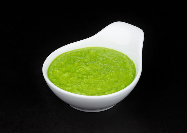 Wasabi in white bowl on black background Premium Photo