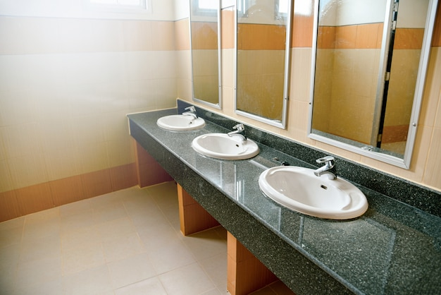Wash sink basin and mirrors in the white bathroom in public toilet Premium Photo