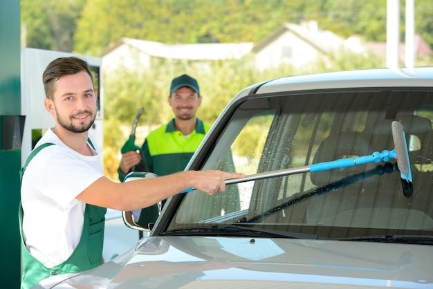 Washing car window while filling petrol cars at gas station Premium Photo
