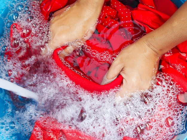Washing clothes with hands using detergents, soak red fabric in laundry detergent and water from tap water in blue wash basin. Premium Photo