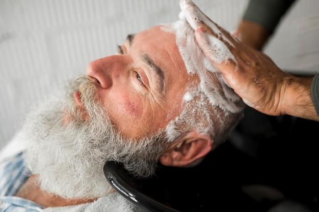 Washing hair of elderly man in barbershop Free Photo