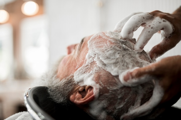 Washing hair of senior male in barbershop Free Photo