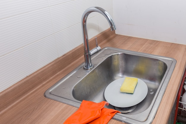 Washing plates with detergent and gloves Premium Photo