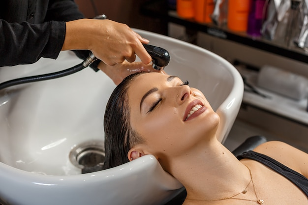 Washing procedure. beautiful young woman with hairdresser washing head at hair salon. Premium Photo