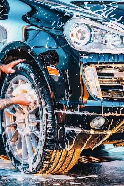 車を洗う。洗車場で黒い車を洗う。きれいな車 Premium写真