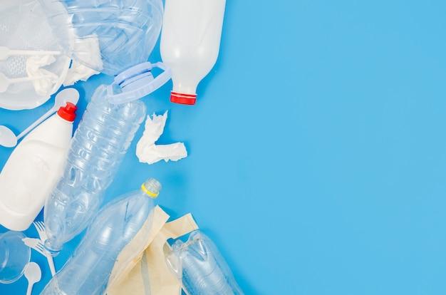 파란색 배경 위에 플라스틱 쓰레기와 구겨진 종이 낭비 프리미엄 사진