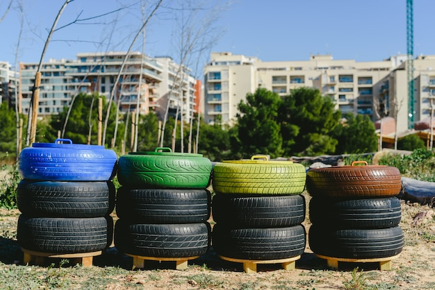 Wastebaskets to recycle paper, plastic and organic materials made with old recycled tires and painted colors, concept of sustainability and recycling. Premium Photo