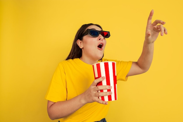 Watching cinema in 3d-eyewear with popcorn. caucasian woman on yellow studio background. beautiful brunette model in casual style. concept of human emotions, facial expression, sales, ad, copyspace. Free Photo