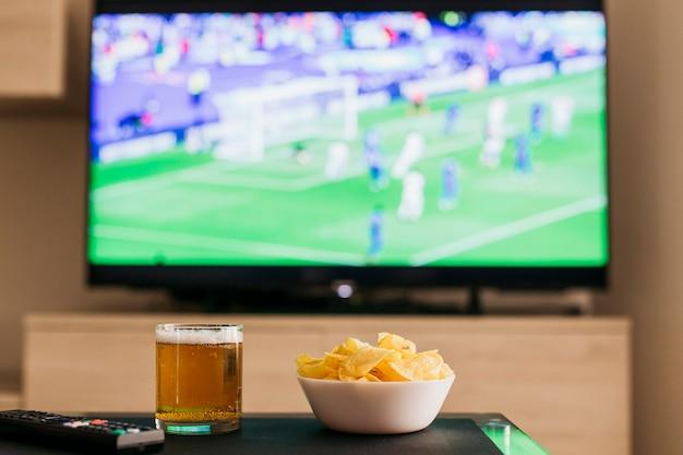 Viendo el concepto de fútbol con cerveza y patatas fritas Foto Gratis