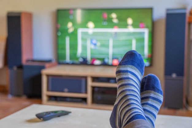 Watching a soccer match on tv with the feet on the table where the remote control is located Premium Photo