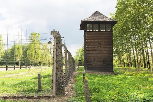 Сторожевая башня и забор из колючей проволоки на территории немецкого концлагеря освенцим ii, польша. Premium Фотографии