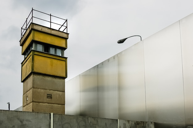 Watchtower next to a wall on a border to control illegal immigrants. Premium Photo