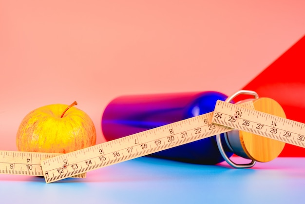 Water bottle, apple and measuring tape isolated on colorful background in studio, healthy life concept. Premium Photo