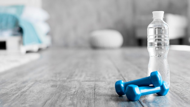Water bottle next to dumbbells Free Photo