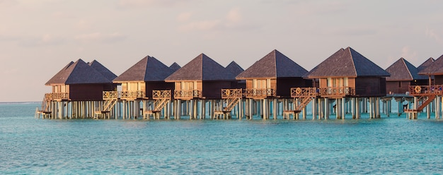 Water bungalows and wooden jetty on maldives Premium Photo
