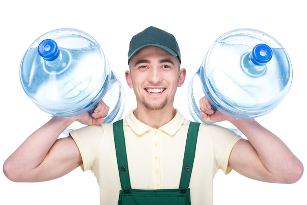Water delivery courier is holding a two bottles. Premium Photo