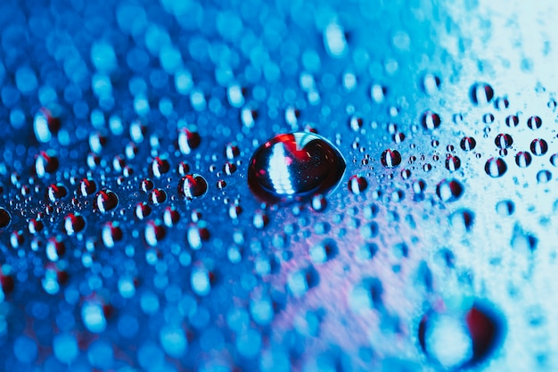 Water drop on the bright blue bokeh background Free Photo