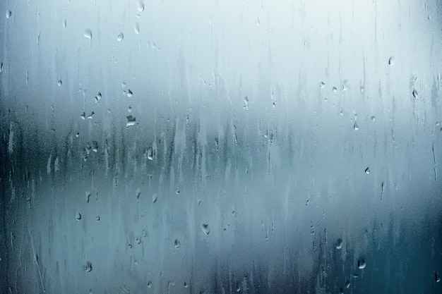 Water droplet texture background, rain falling from the sky and drop on glass rooftop Premium Photo