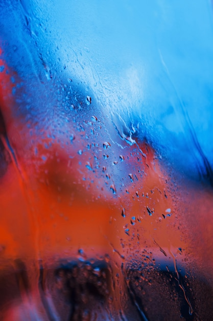 Water droplets on neon glass background. red and blue colors Free Photo
